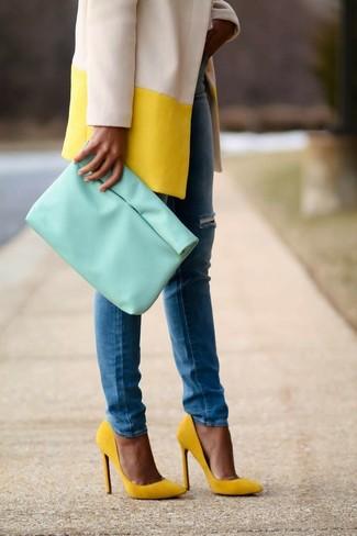 Cómo combinar: abrigo amarillo, vaqueros pitillo azules, zapatos de tacón de ante amarillos, cartera sobre de cuero en verde menta
