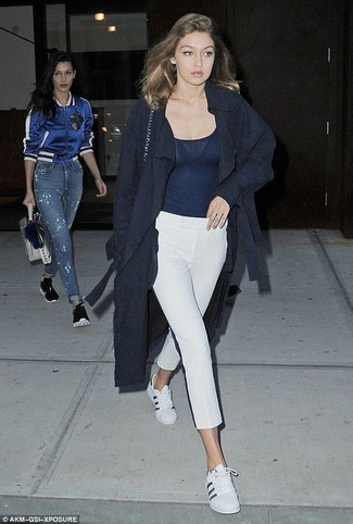 Cómo combinar: abrigo azul marino, camiseta sin manga azul marino, pantalón capri blanco, tenis de cuero blancos