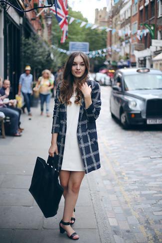 Cómo combinar: abrigo a cuadros azul marino, vestido recto blanco, sandalias de tacón de cuero negras, bolsa tote de cuero negra