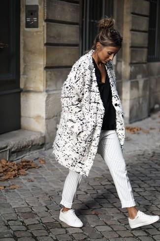 Cómo combinar: abrigo de lana rizada blanco, blusa de manga larga negra, pantalón de vestir de rayas verticales en blanco y negro, tenis de cuero blancos