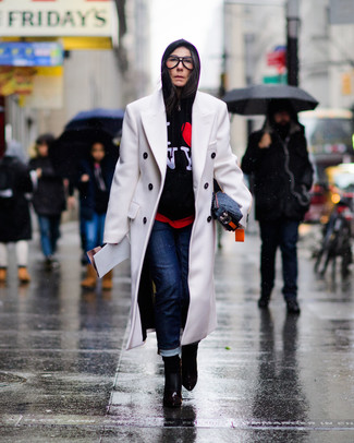 Cómo combinar: abrigo blanco, sudadera con capucha estampada negra, vaqueros azul marino, botines de cuero negros