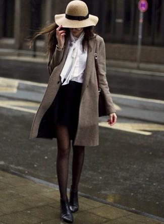 Cómo combinar: abrigo verde oliva, blusa de botones blanca, minifalda negra, botines de cuero negros