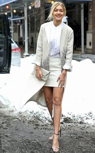 Cómo combinar: abrigo en beige, blusa de botones blanca, minifalda en beige, sandalias de tacón de cuero doradas