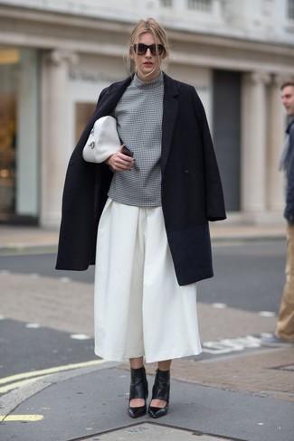 Cómo combinar: abrigo negro, blusa de manga corta a cuadros gris, falda pantalón blanca, botines de cuero con recorte negros