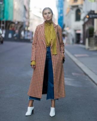 Cómo combinar: abrigo a cuadros naranja, blusa de manga larga a lunares amarilla, falda pantalón vaquera azul, chinelas de cuero blancas
