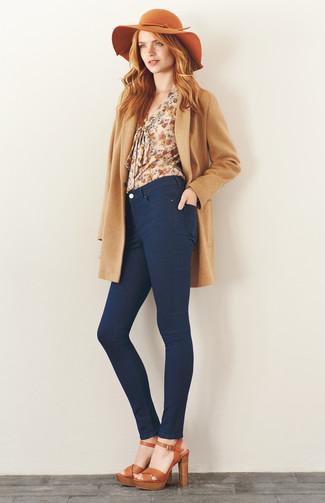 Cómo combinar: abrigo marrón claro, blusa de manga larga con print de flores en beige, vaqueros pitillo azul marino, sandalias de tacón de cuero marrón claro