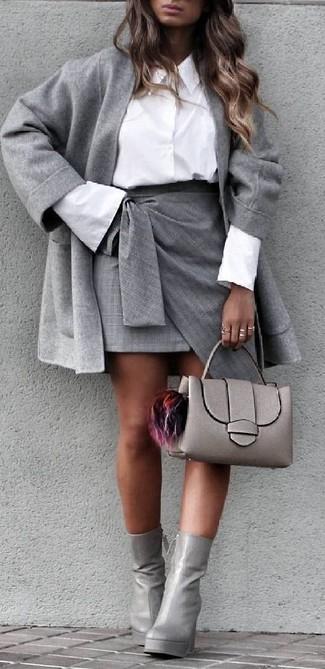 Cómo combinar: abrigo gris, camisa de vestir blanca, minifalda con recorte gris, botines de cuero grises