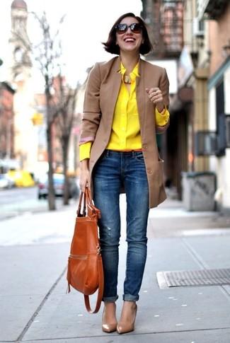 Cómo combinar: abrigo marrón claro, camisa de vestir amarilla, vaqueros pitillo desgastados azules, zapatos de tacón de cuero marrónes