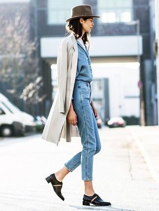 Cómo combinar: abrigo en beige, camisa vaquera azul, vaqueros azules, zapatos oxford de cuero negros