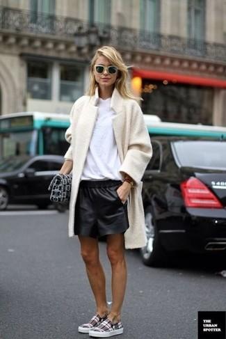 Cómo combinar: abrigo de forro polar en beige, camiseta con cuello circular blanca, pantalones cortos de cuero negros, zapatillas slip-on de tartán grises