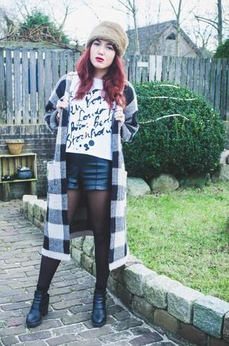 Cómo combinar: abrigo a cuadros en blanco y negro, camiseta con cuello circular estampada en blanco y negro, pantalones cortos de cuero negros, botines de cuero negros
