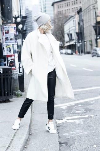 Intenta ponerse un abrigo blanco y unos pantalones de pijama de cuero negros para conseguir una apariencia glamurosa y elegante. Haz este look más informal con tenis en blanco y negro.