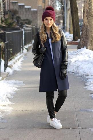 Cómo combinar: abrigo de cuero negro, camiseta con cuello circular blanca, pantalones pitillo de cuero negros, tenis de cuero blancos