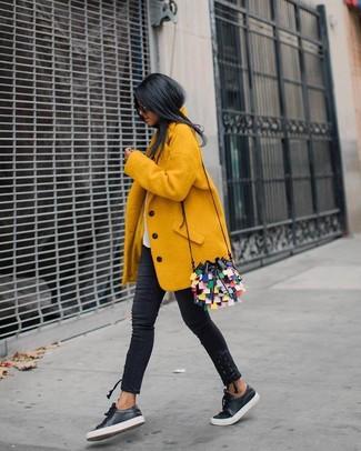 Cómo combinar: abrigo amarillo, camiseta con cuello circular blanca, vaqueros pitillo negros, tenis de cuero negros