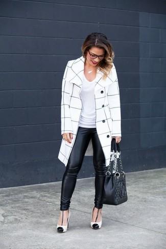 Cómo combinar: abrigo a cuadros en blanco y negro, camiseta con cuello en v blanca, leggings de cuero negros, zapatos de tacón de cuero en blanco y negro