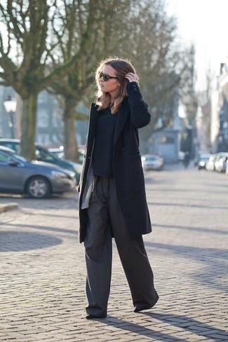 Empareja un abrigo negro con unos pantalones anchos en gris oscuro para sentirte con confianza y a la moda. Botines de ante negros son una opción muy buena para completar este atuendo.