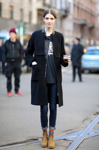 Cómo combinar: abrigo negro, chaqueta motera de cuero negra, camiseta con cuello circular estampada en negro y blanco, vaqueros pitillo azul marino