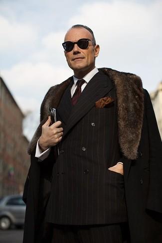 Cómo combinar: abrigo con cuello de piel negro, blazer cruzado de rayas verticales negro, camisa de vestir blanca, pantalón de vestir de rayas verticales negro