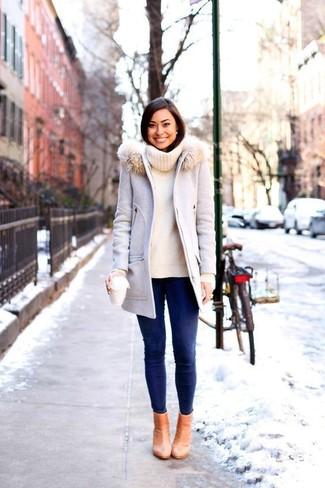 Cómo combinar: abrigo con cuello de piel gris, jersey con cuello vuelto holgado en beige, vaqueros pitillo azul marino, botines de cuero marrón claro