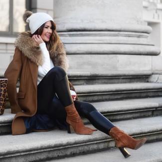 Cómo combinar: abrigo con cuello de piel marrón, jersey con cuello circular blanco, leggings de cuero negros, botines de ante marrónes