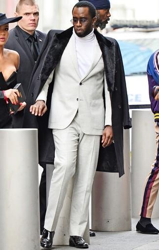 Cómo combinar: abrigo con cuello de piel negro, traje en beige, jersey de cuello alto blanco, botines chelsea de cuero negros