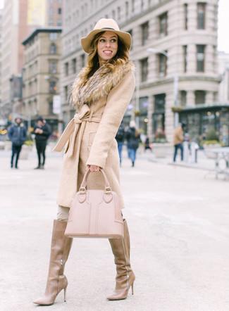 Cómo combinar: abrigo con cuello de piel en beige, pantalones pitillo en beige, botas de caña alta de cuero marrón claro, bolsa tote de cuero en beige