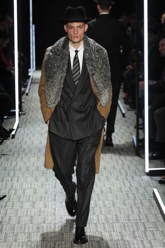 Cómo combinar: abrigo con cuello de piel marrón, traje de rayas verticales negro, camisa de vestir blanca, botas formales de cuero negras