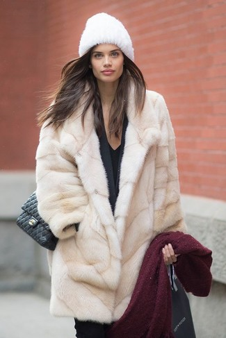 Cómo combinar: abrigo de piel en beige, blazer negro, camiseta con cuello en v negra, pantalones pitillo negros