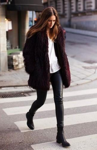 Cómo combinar: abrigo de piel burdeos, camiseta con cuello circular blanca, leggings de cuero negros, botines de cuero negros