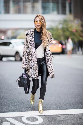 Cómo combinar: abrigo de piel de leopardo en beige, camiseta de manga larga en blanco y negro, vaqueros pitillo de cuero negros, botines de cuero dorados