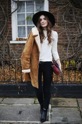 Cómo combinar: abrigo de piel de oveja marrón claro, jersey con cuello circular blanco, vaqueros pitillo negros, botines de cuero negros