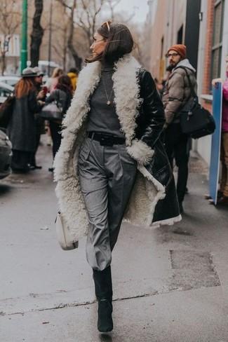 Algo tan simple como emparejar un abrigo de piel de oveja negro y blanco con un pantalón de pinzas gris puede distinguirte de la multitud. Complementa tu atuendo con botas a media pierna de ante negras.