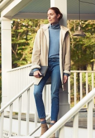 Cómo combinar: abrigo de piel de oveja en beige, jersey de cuello alto celeste, vaqueros azules, botines de ante marrón claro