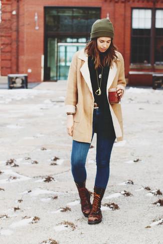 Cómo combinar: abrigo de piel de oveja en beige, jersey de cuello alto negro, vaqueros pitillo azules, botas planas con cordones de cuero en marrón oscuro