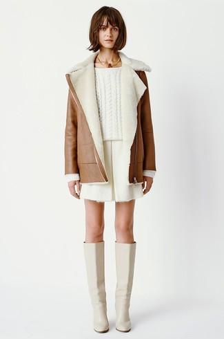 Cómo combinar: abrigo de piel de oveja marrón, jersey de ochos blanco, pantalones cortos blancos, botas de caña alta de cuero en beige