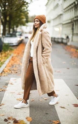 Cómo combinar un abrigo de piel en beige: Intenta ponerse un abrigo de piel en beige y un pantalón de vestir en tabaco y te verás impresionante en cualquier lugar y en cualquier momento. Tenis de cuero blancos añadirán interés a un estilo clásico.