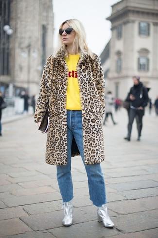 Cómo combinar: abrigo de piel de leopardo marrón claro, jersey con cuello circular estampado amarillo, vaqueros azules, botines de cuero plateados