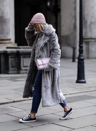 Cómo combinar: abrigo de piel gris, jersey de cuello alto de punto gris, vaqueros pitillo desgastados azul marino, tenis de lona en negro y blanco