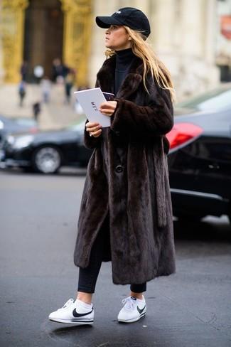 Cómo combinar: abrigo de piel en marrón oscuro, jersey de cuello alto negro, vaqueros pitillo negros, tenis de cuero blancos