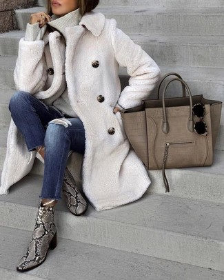 Cómo combinar: abrigo de piel blanco, jersey de cuello alto gris, vaqueros pitillo desgastados azul marino, botines de cuero con print de serpiente grises