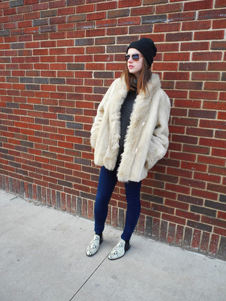Cómo combinar: abrigo de piel en beige, jersey de cuello alto en gris oscuro, vaqueros pitillo azules, botines de cuero con print de serpiente grises