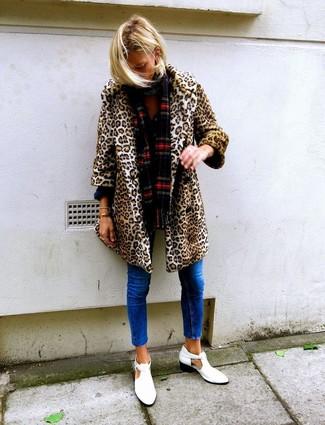 Cómo combinar: abrigo de piel de leopardo marrón claro, vaqueros pitillo azules, botines de cuero con recorte blancos, bufanda de tartán roja