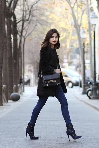 Cómo combinar: abrigo de piel negro, vaqueros pitillo azules, botines de ante azul marino, bolso de hombre de cuero negro