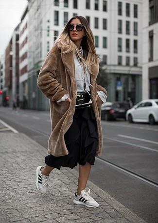 Cómo combinar: abrigo de piel marrón, sudadera con capucha gris, falda midi plisada negra, tenis de cuero blancos