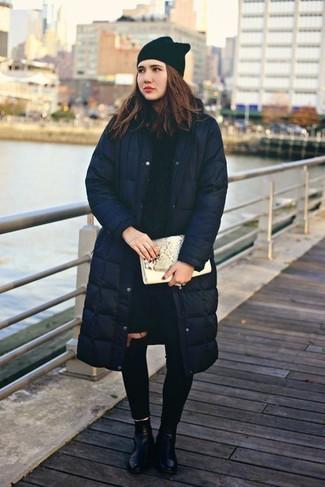 Cómo combinar: abrigo de plumón azul marino, jersey de ochos azul marino, vaqueros pitillo desgastados negros, botines de cuero negros