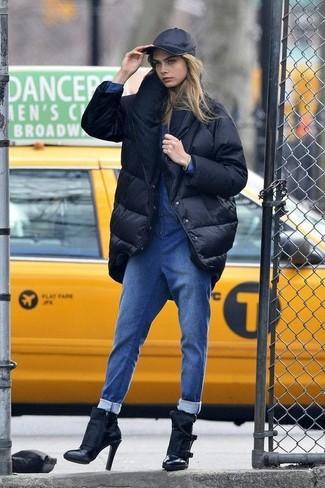 Cómo combinar: abrigo de plumón negro, mono vaquero azul, botines de cuero negros, gorra inglesa negra