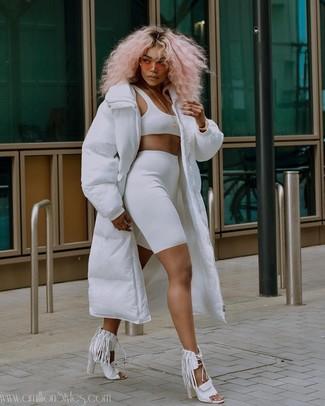 Cómo combinar: abrigo de plumón blanco, top corto blanco, mallas ciclistas blancas, sandalias de tacón de cuero сon flecos blancas