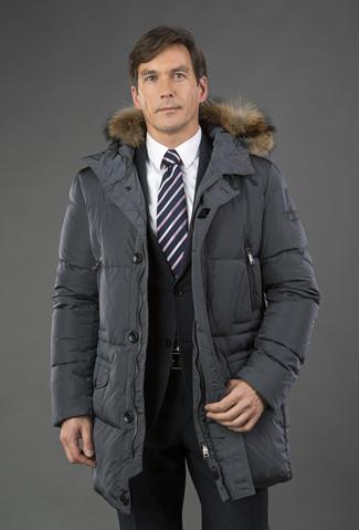 Cómo combinar: abrigo de plumón en gris oscuro, traje negro, camisa de vestir blanca, corbata de rayas verticales en negro y blanco