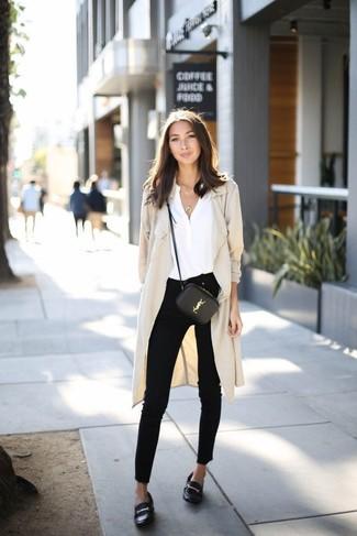 Cómo combinar: abrigo duster en beige, blusa de manga larga de seda blanca, vaqueros pitillo negros, mocasín de cuero negros