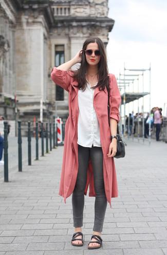 Cómo combinar: abrigo duster rosado, camisa de vestir blanca, vaqueros pitillo en gris oscuro, sandalias planas de cuero negras